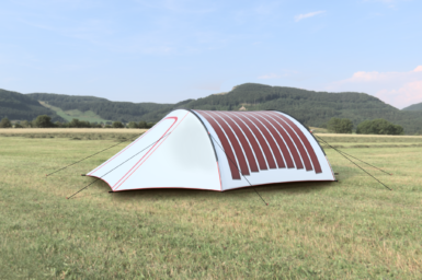 A tent pitched in a remote grassy area with flexible solar panels