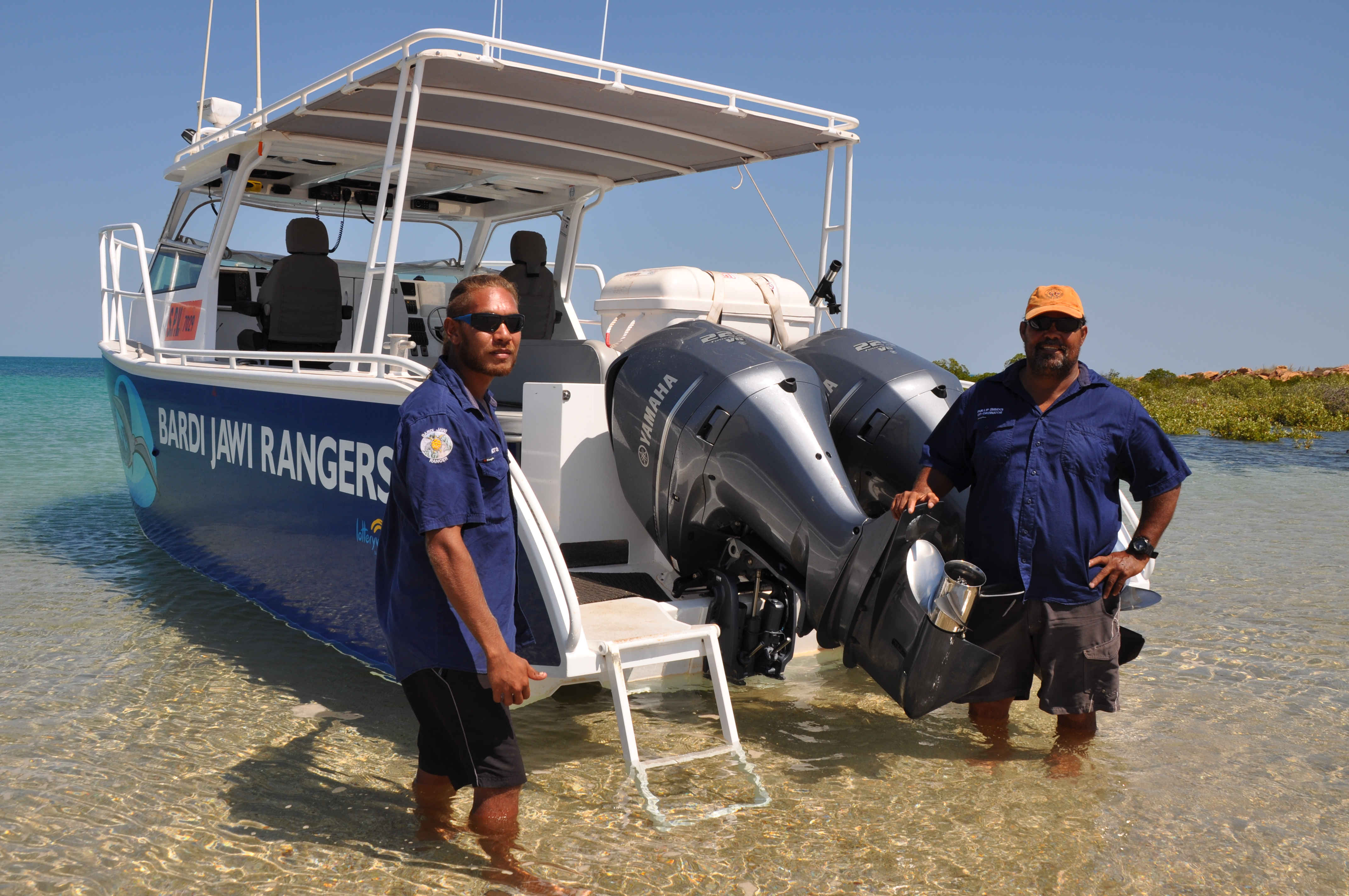 Two Bardi Jawi Indigenous rangers standing in front of a Bardi Jawi boat