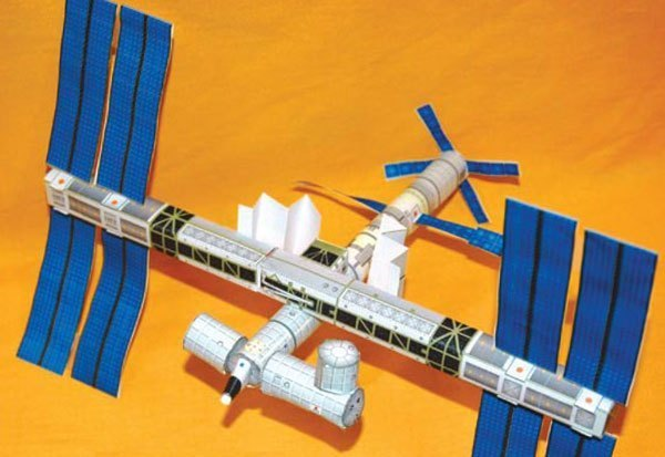 paper model of the international space station on a yellow background