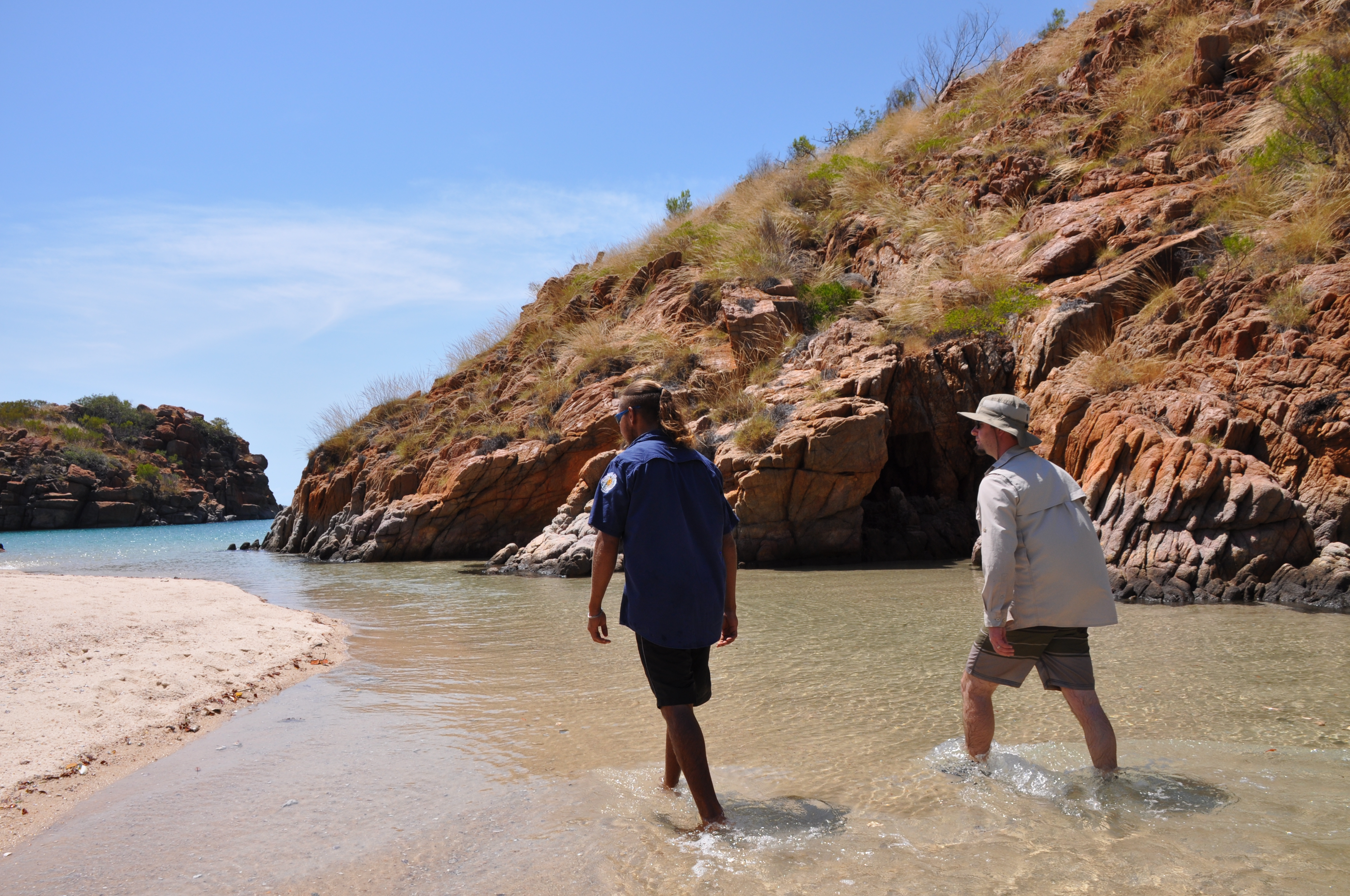 Two people walking in a water way in the Kimberley