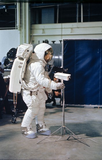 Person in astronaut suit on earth indoors testing small white camera on tripod.