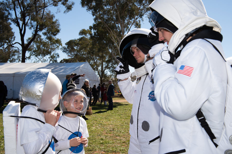 Two young kids in astronaut costumes talking to two adults in astronaut costumes.