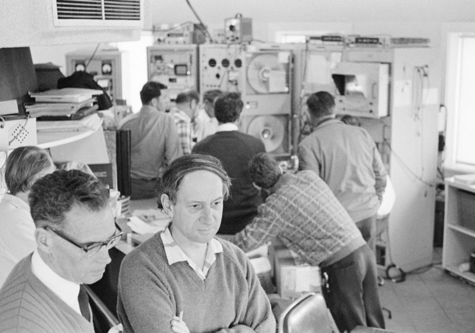 Black and white image of two men observing a screen with people working in control room behind them.