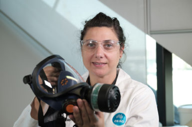 Researcher in lab coat holding a respirator mask