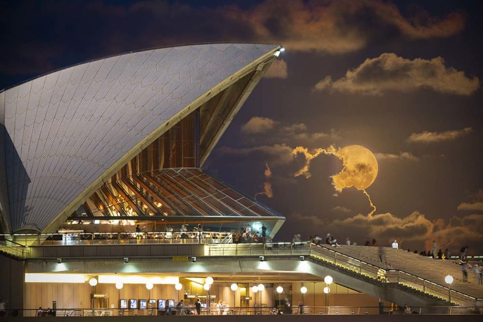Photograph of the Moon, large and yellow, behind the Sydney Opera House