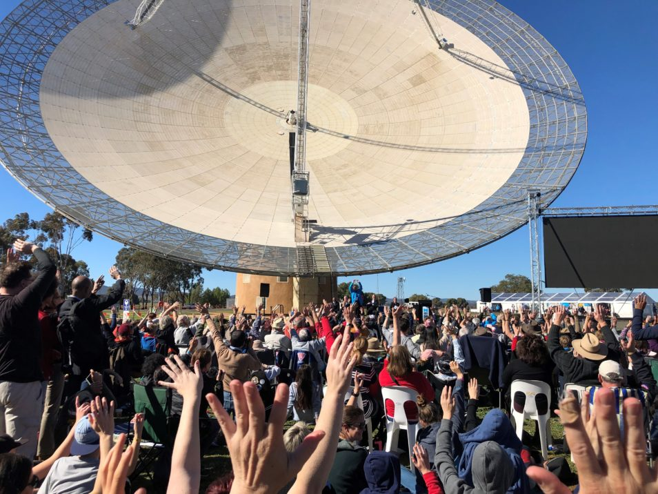 Crowd of people raising hands in front of the Dish