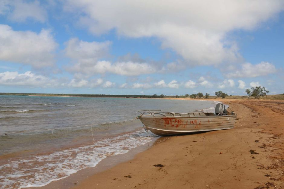 A tinny boat rests on the shore as waves lap up against it.