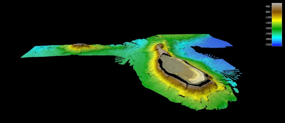 A seafloor mapping (bathymetry) image of Frederic Reef. A black background with blue green mountains, going yellow to brown to indicate the height of the sea mountains. There is a plateau in the middle of the mountain.