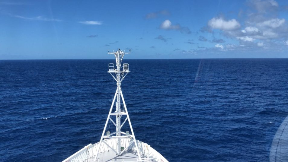 The stern of a white ship looking over a deeper blue ocean and a lighter blue sky. There are minimal clouds in the top right of the image.