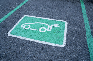 A photograph of a green parking reserved sign for electric vehicle chargin.