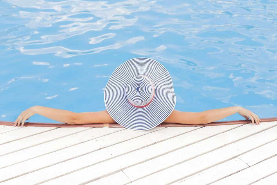 A woman wearing a large white and blue striped sun hat leaning against the edge of a swimming pool with her back to the camera