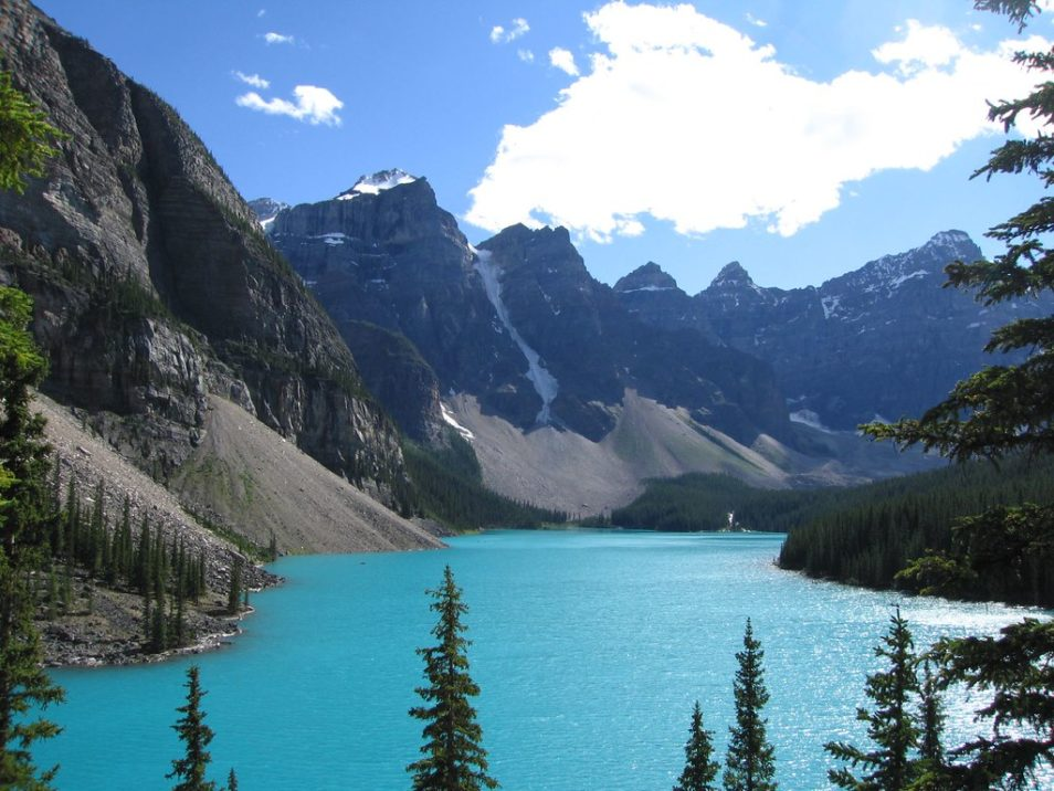 The Candanian Rockies wildreness area. A bright blue lake surrounded by snow-topped mountains and trees