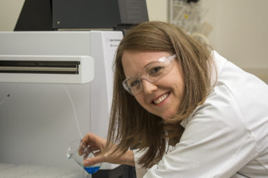 Laura Kuhar in a lab coat in a lab.