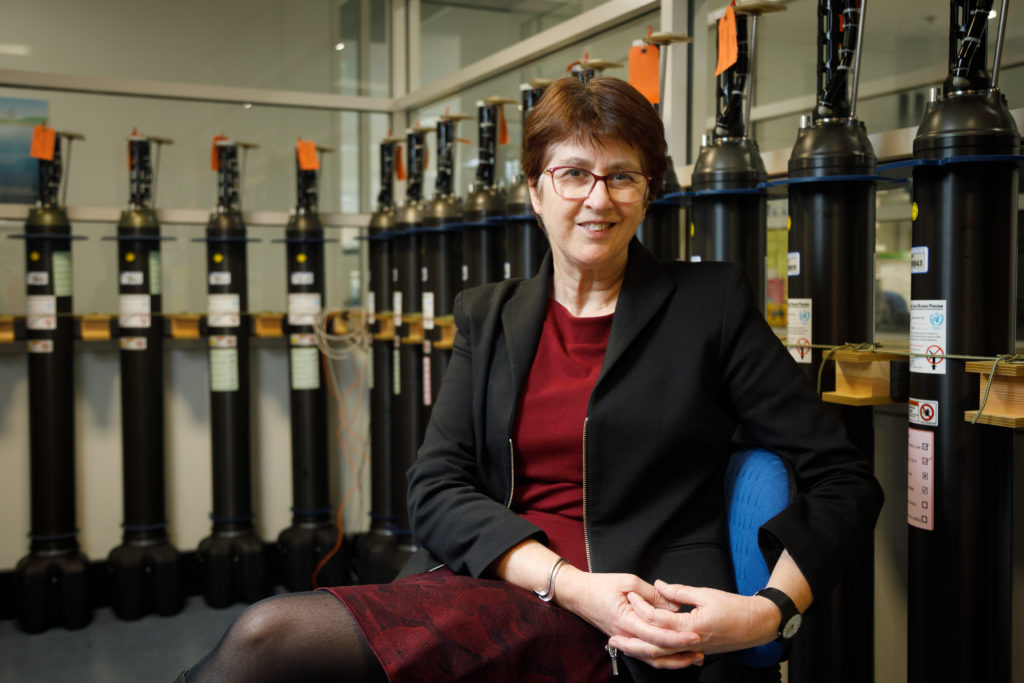 New ATSE fellow Dr Helen Cleugh sitting on a chair. There are canisters of gas hanging on the walls around her in rows