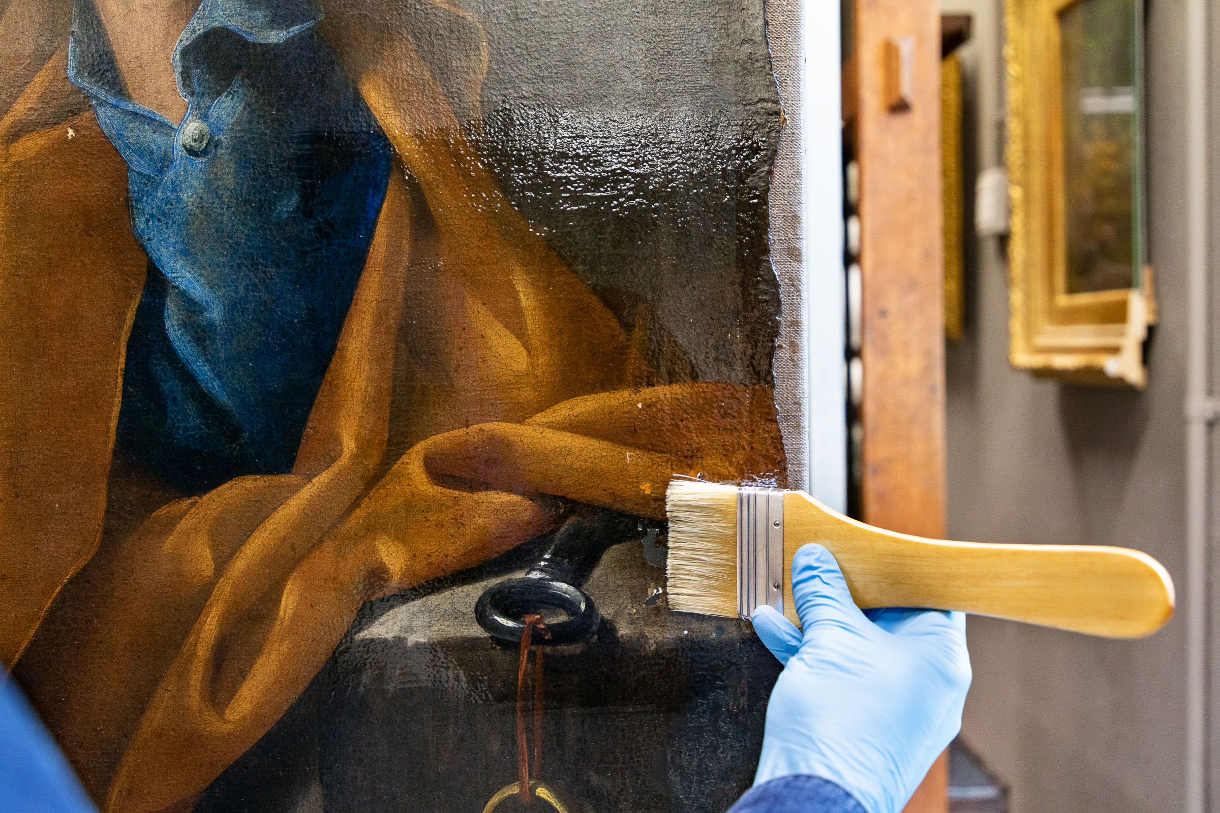 art resin is applied to a painting with a wide brush by a gloved hand