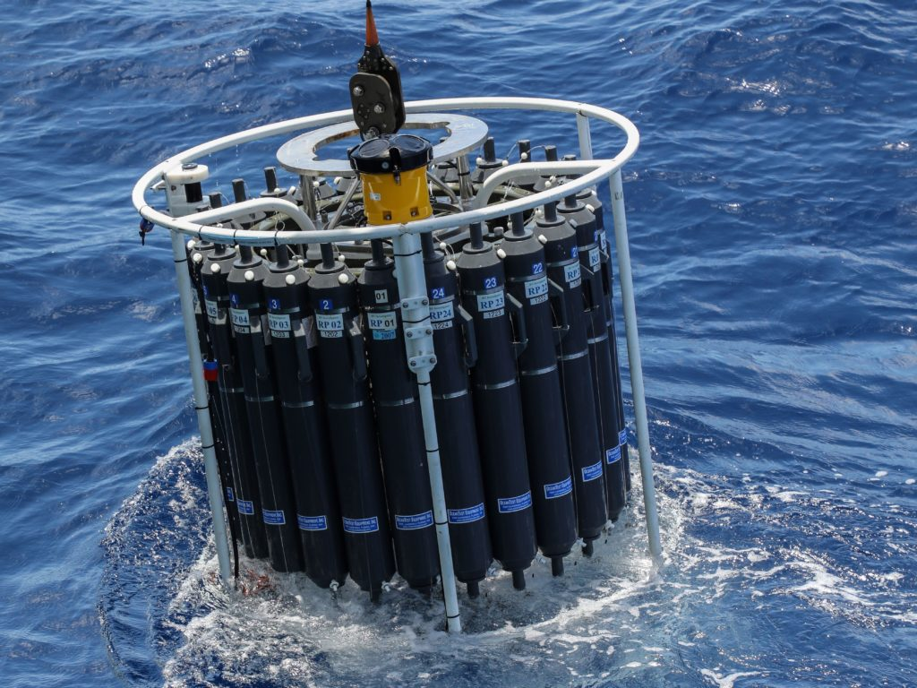 A large cylinder filled with black bottles is lowered into the ocean