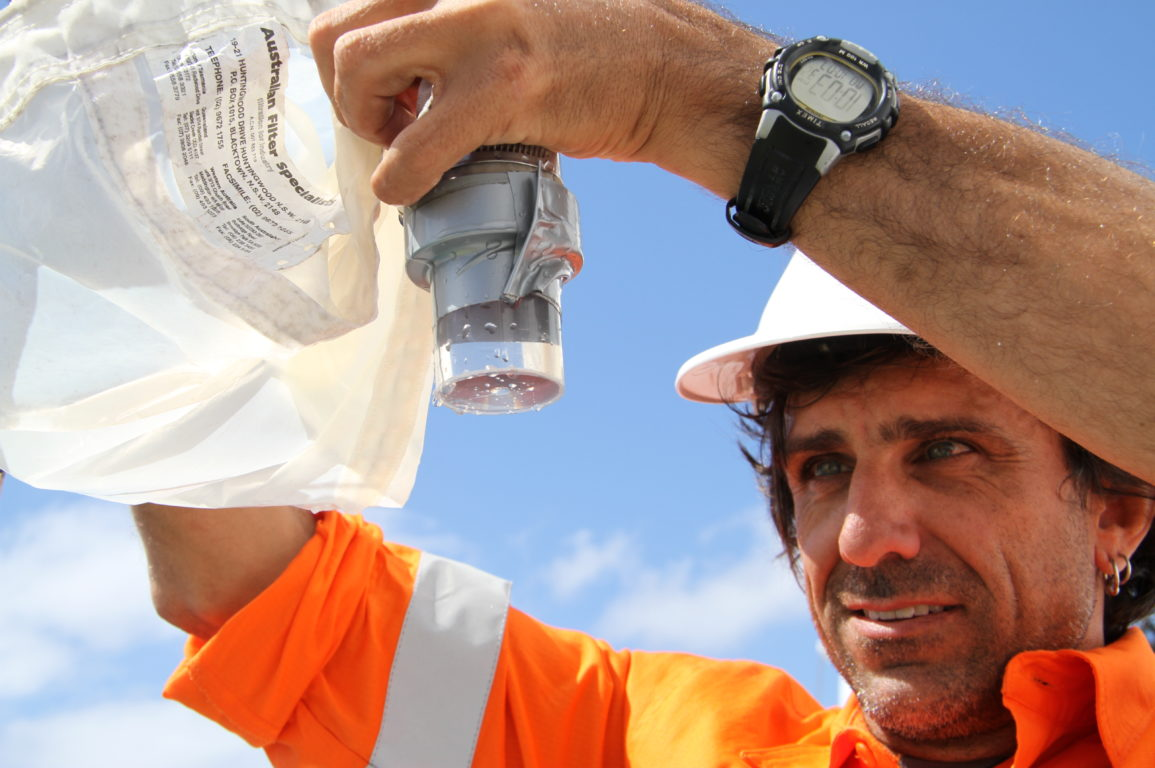 Man in high-visibility orange shirt and hard hat looking at a water sample in a container