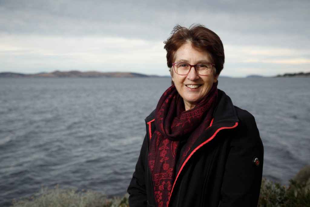 New ATSE Fellow Dr Helen Cleugh standing in front of a body of water. She is wearing a jacket and scarf