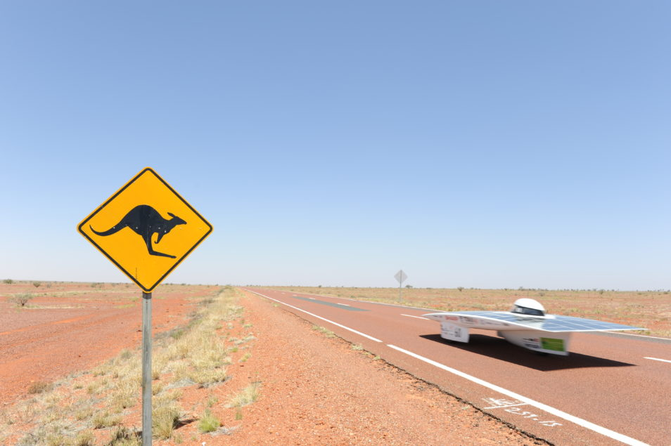 a flat rocketship-like car zooming down a reddy orange outback road. There is a yellow kangaroo road sign in the foreground.