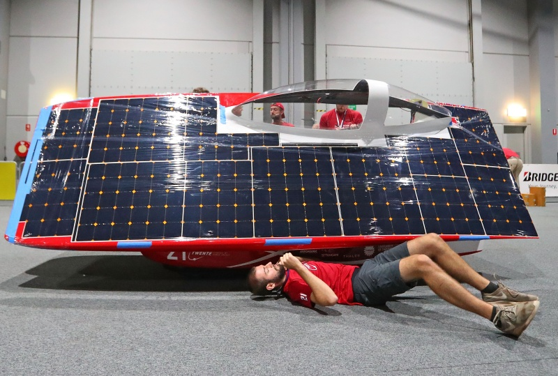 A red vehicle with a massive solar panel taking up the entire side of it. A man is on his back with his arm under the vehicle.