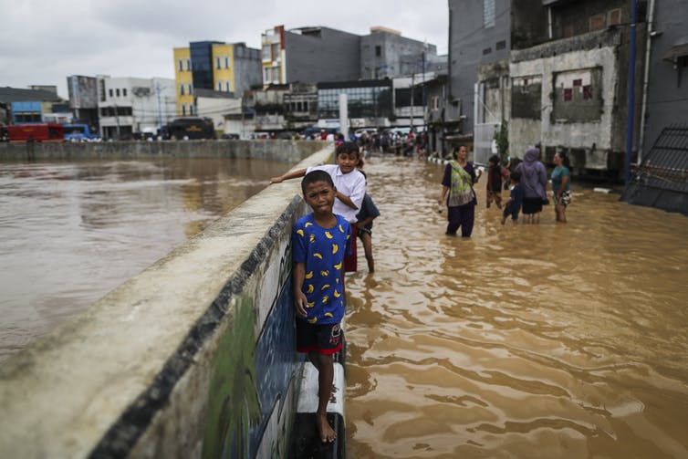 Young children standing in brown flood water in Jakarta