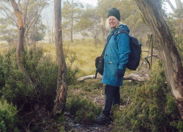 Penny Whetton in a coat and beanie standing among trees