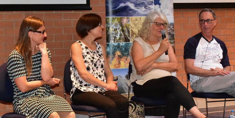 Penny Whetton taking part in a panel discussion. She's speaking into the microphone while other panelists look on