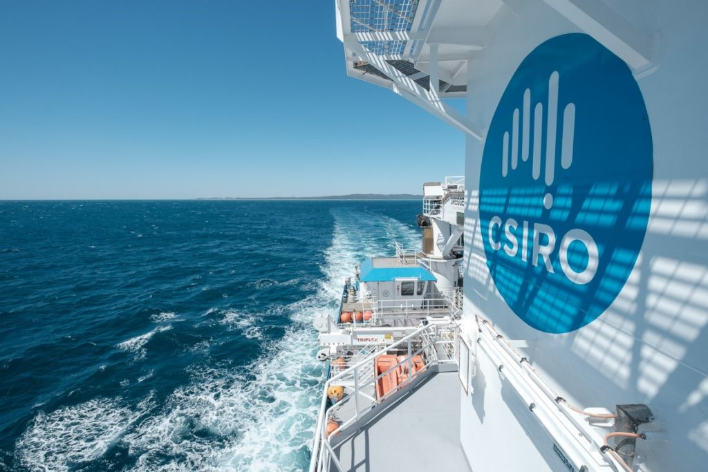 A white boat with a large CSIRO logo on the side. It is on the ocean. You can see the deck with scientists and lifeboats on board. EAC