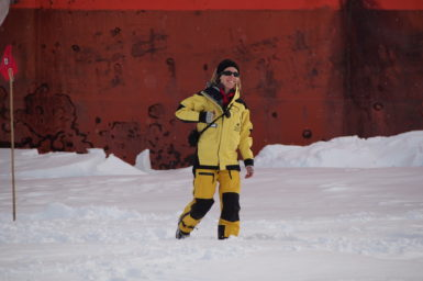 Jess Melbourne-Thomas undertaking sea ice ecosystem field work in East Antarctica. She wears a yellow suit and is surrounded by snow.