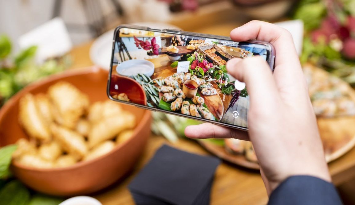 Person taking a photo of food using their phone