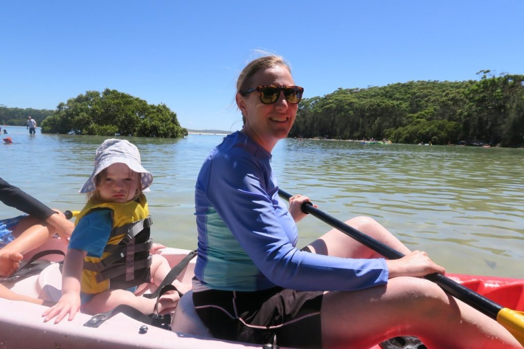A woman kayaking with a little girl in the back of the kayak