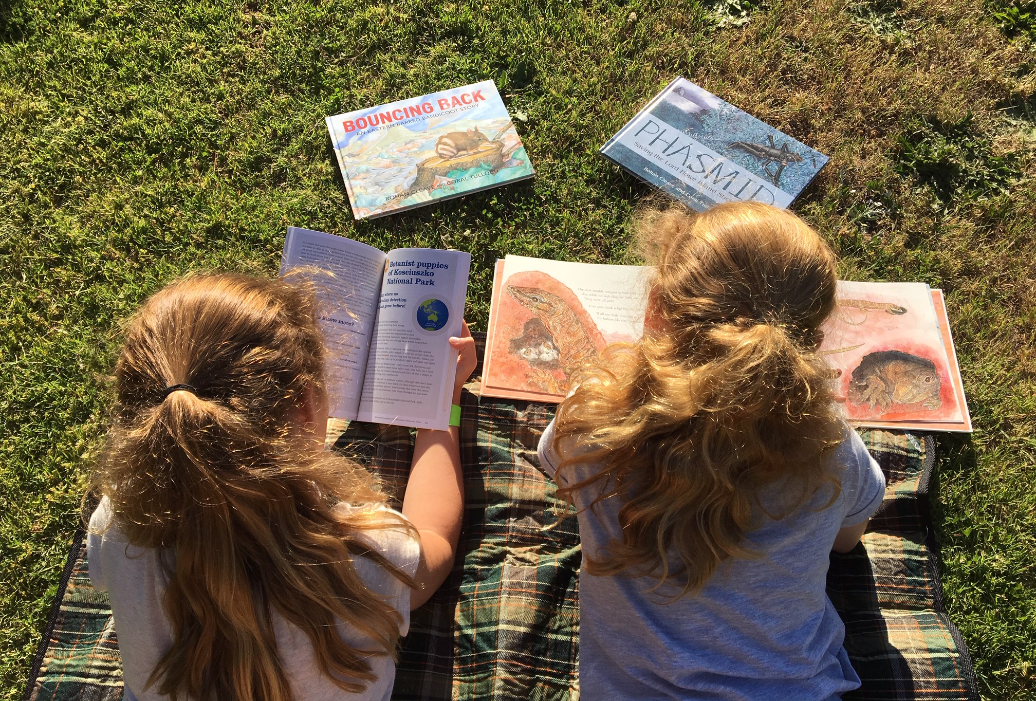 Two children reading books on the grass. photo taken from above