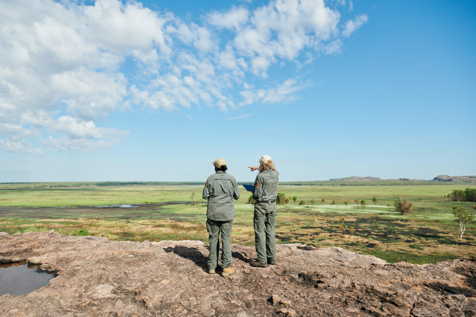 Two people in uniform looking out into the countryside.