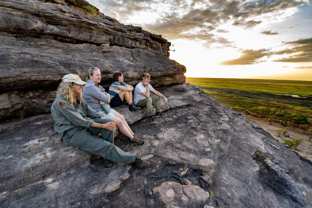 Four people sitting on a rocky outcrop, looking out to the wetlands of Kakadu.