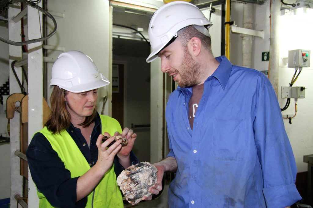 Two researchers in hard hats looking at underwater rock samples