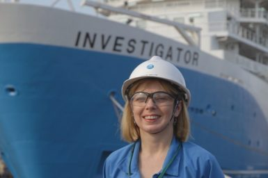 Toni Moate stands in front of docked research vessel wearing hardhat and safety glasses.