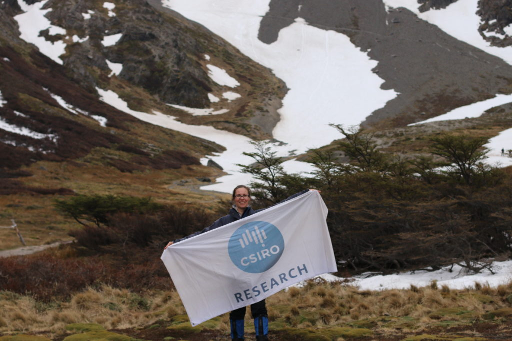Researcher Clothilde Langlais holding a CSIRO research flag with snowy mountains in the background