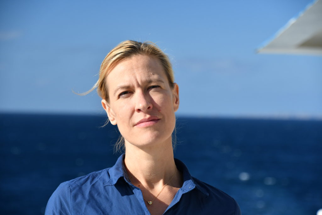 A white woman with blonde hair staring directly into the camera. She's wearing a blue shirt with the ocean in the background.
