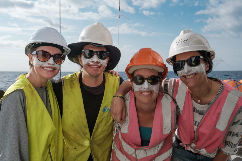 A group of people wearing sunglasses, hardhats and zinc looking and smiling at the camera on board RV Investigator.