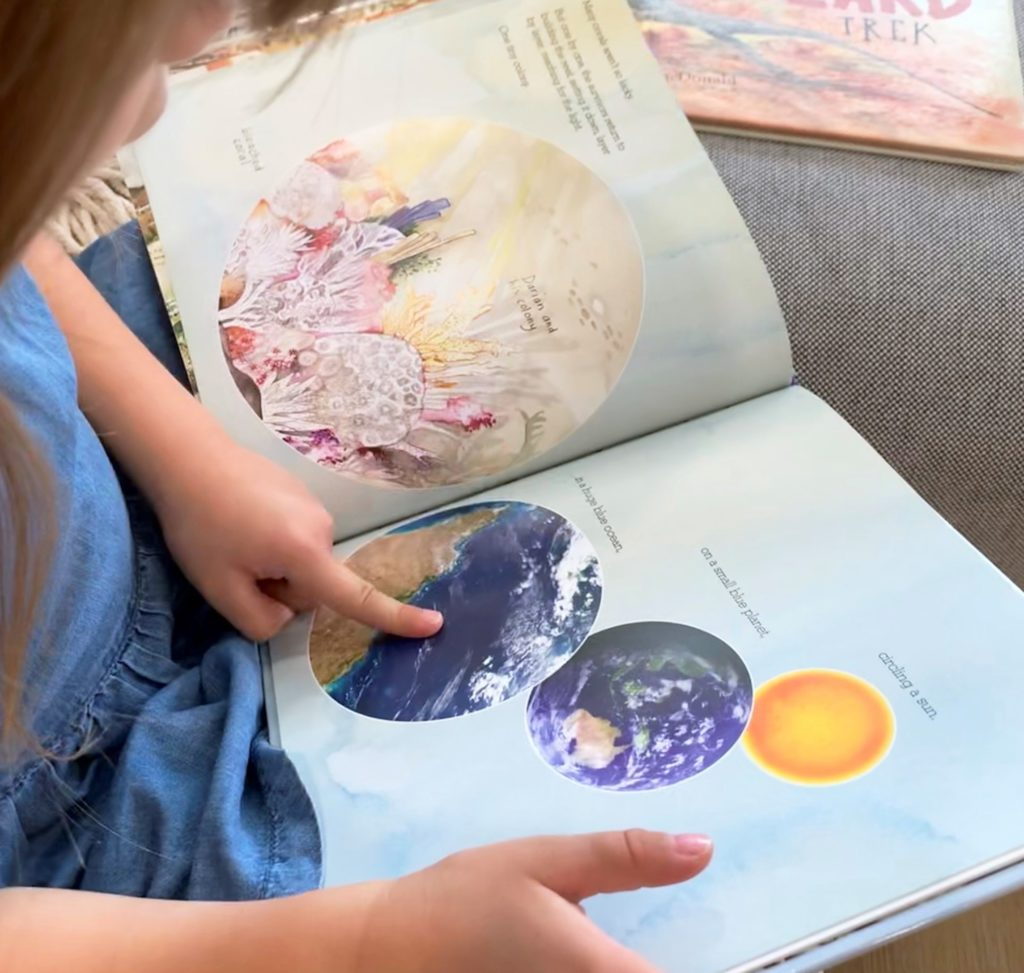 young girl reading a book and pointing at a page. summer reads