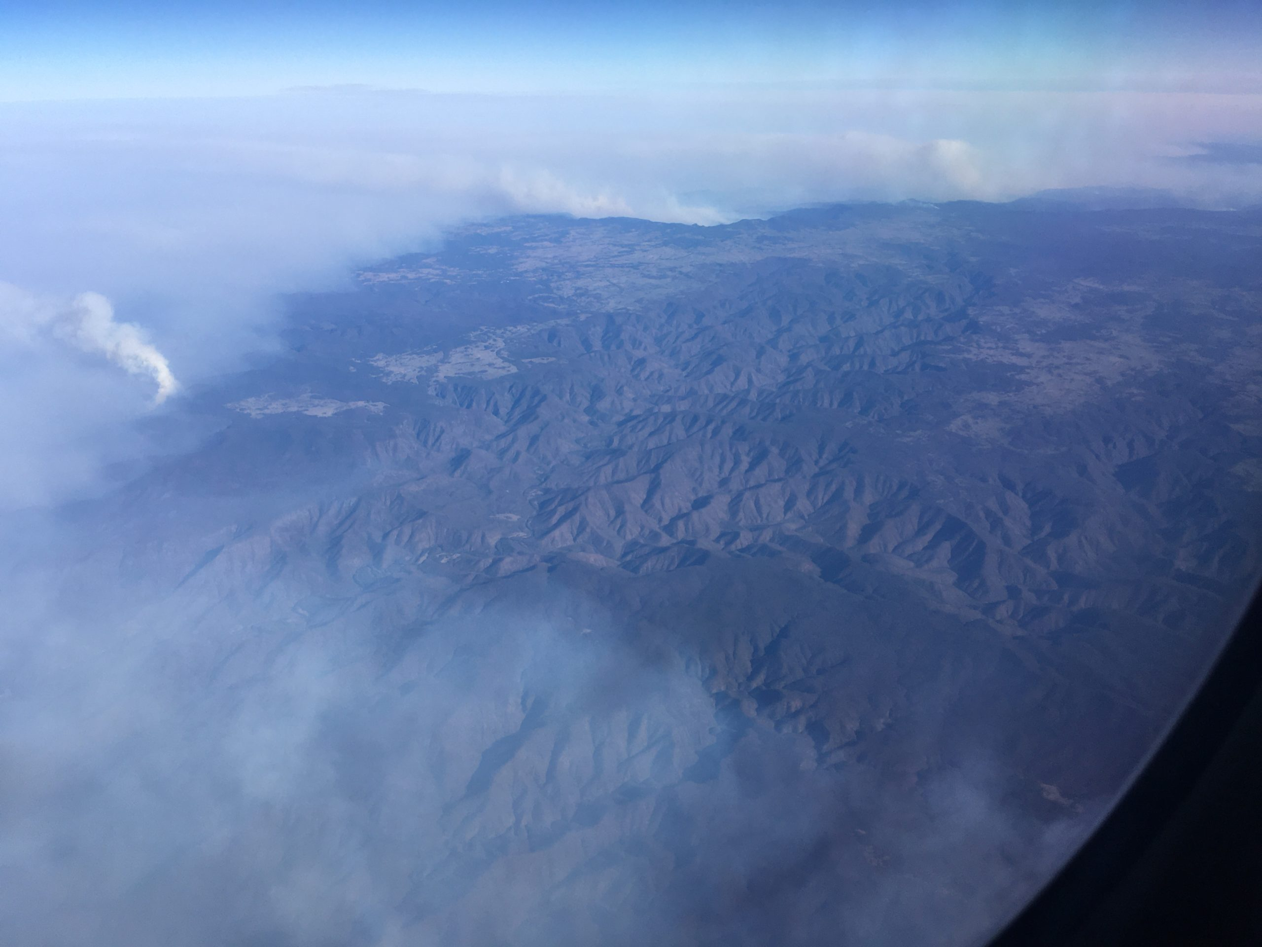 arial photo of mountainous landscape showing smoke from bushfire