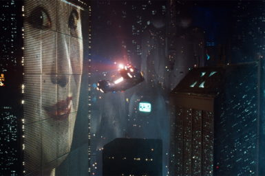 clip from the film Blade Runner showing flying cars around buildings at night. One building has a giant billboard of a lady's face