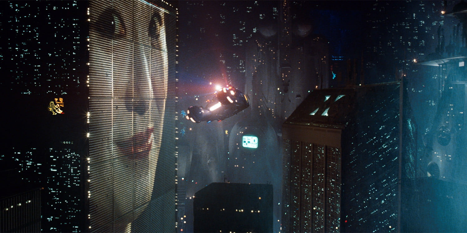 science 2019. Image shows a clip from the film Blade Runner showing flying cars around buildings at night. One building has a giant billboard of a lady's face