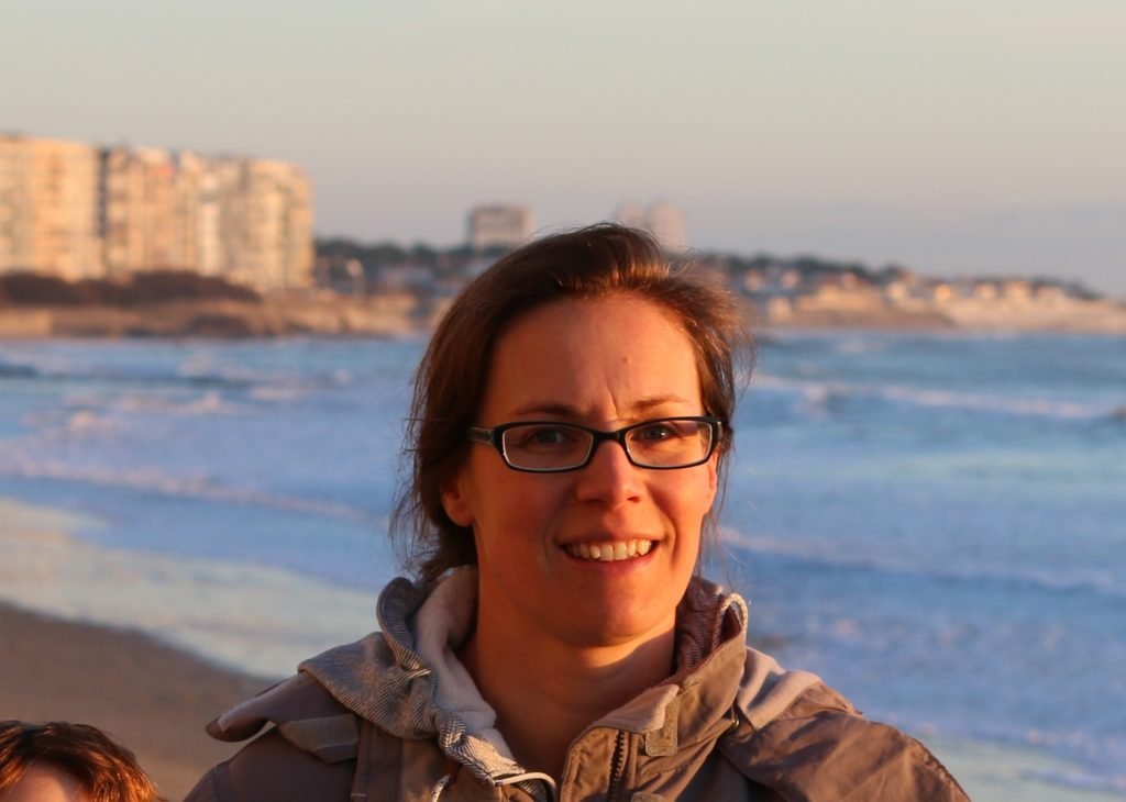 Headshot of researcher Clothilde Langlais with beachside city in the background