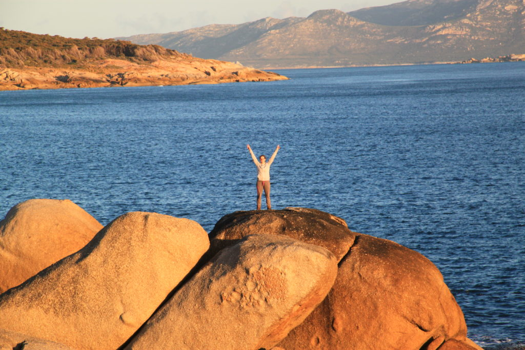 Clothilde Langlais stands on a rock with her arms in the air with water in the background