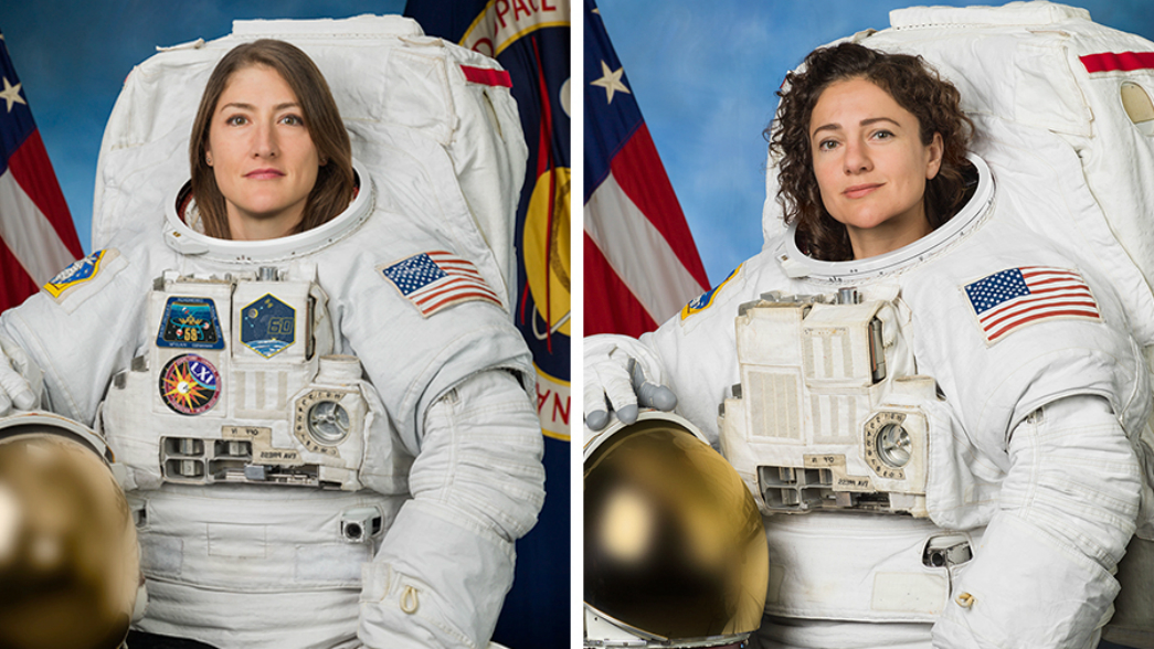 NASA astronauts Koch and Meir in their space suits posing in front of the American flag
