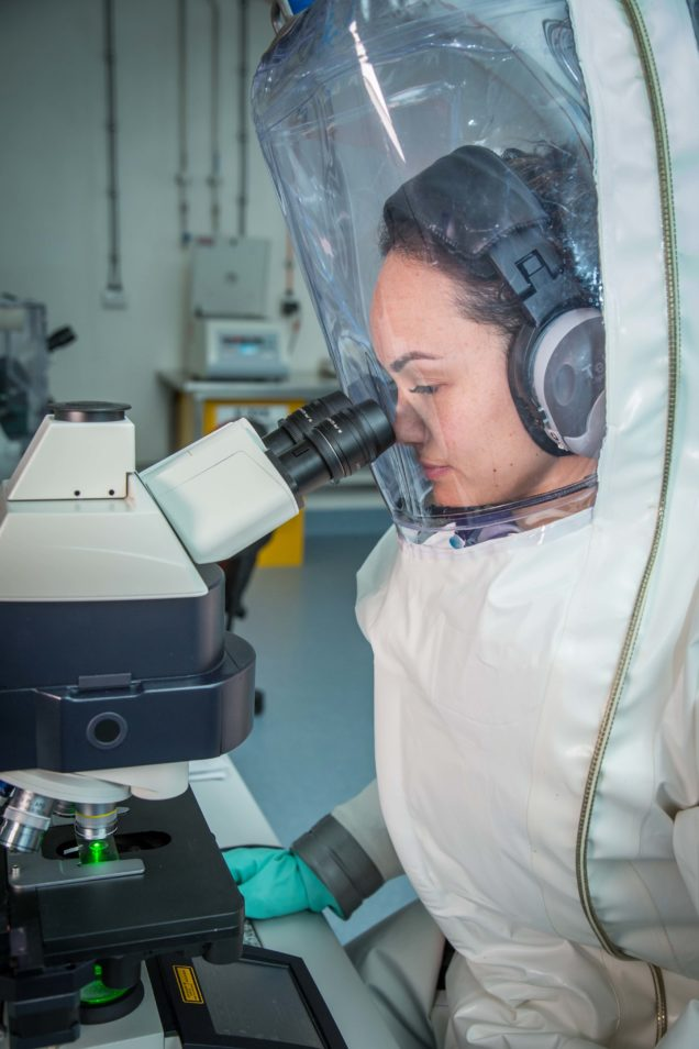 A woman in a sealed, pressurised suit with helmet looks into a microscope. We will be working on coronavirus.