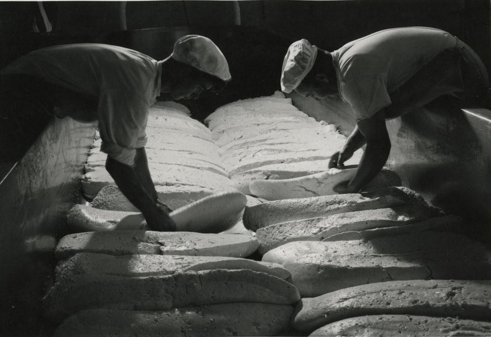 Men handling cheese photographed in B&W
