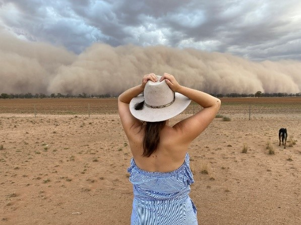 woman holding her hat looking at a huge dust storm