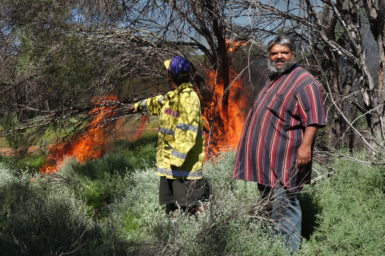Two men light a fire in the bush